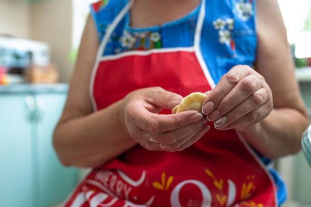 台所の女性が生地とひき肉から餃子を作る