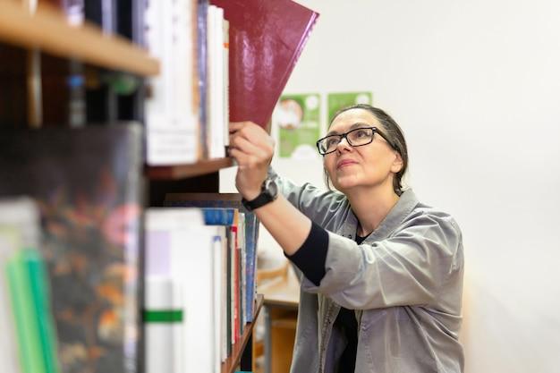 도서관에서 책을 찾는 여성. 중년 여성이 책장에 있는 책을 보고 있습니다. 그녀는 새로운 방향과 방법을 연구합니다.