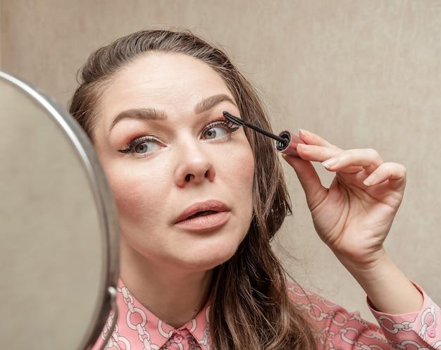 朝、家にいる女性が鏡を見ながら目をペイントします。
