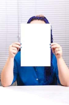 Женщина в офисе держит в руках чистый лист бумаги.