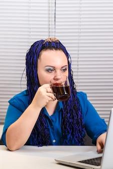 Женщина в офисе с жалюзи и голубыми афро-косичками за компьютером пьет кофе.