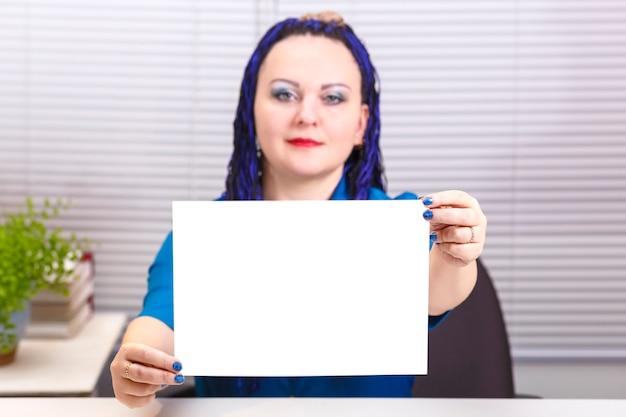 Женщина в офисе с синими афро-косами держит в руках чистый лист бумаги.