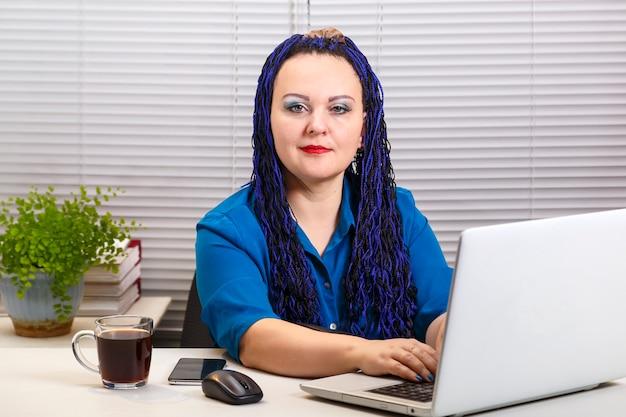 Женщина в офисе с голубыми афро-косами печатает на компьютере.