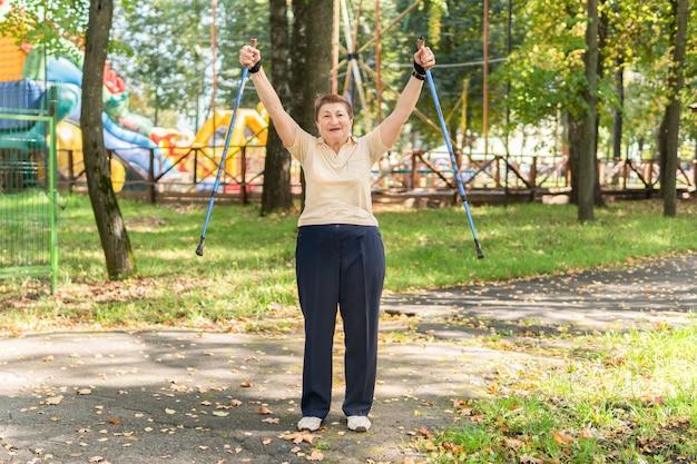 공원에 있는 한 여성이 화창한 여름날 막대기로 북유럽을 걷습니다. 기분이 좋은 시니어 여성이 아침 운동에 참여하고 있습니다.