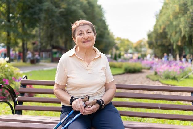 공원의 한 여성이 화창한 여름날 막대기로 북유럽을 걷습니다. 벤치에 앉아 좋은 분위기와 나이 든 여자.