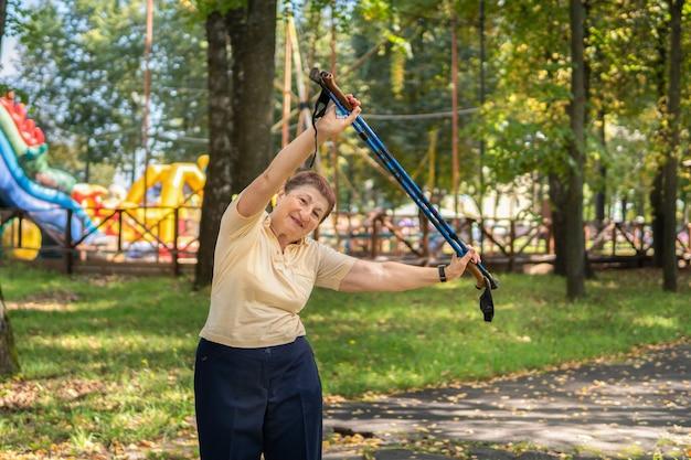 화창한 여름날 공원에서 여자가 막대기로 산책