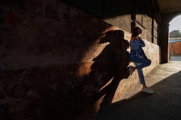 都会的なスタイルの街で日差しの中で女性。街のアーチの女性のシルエット