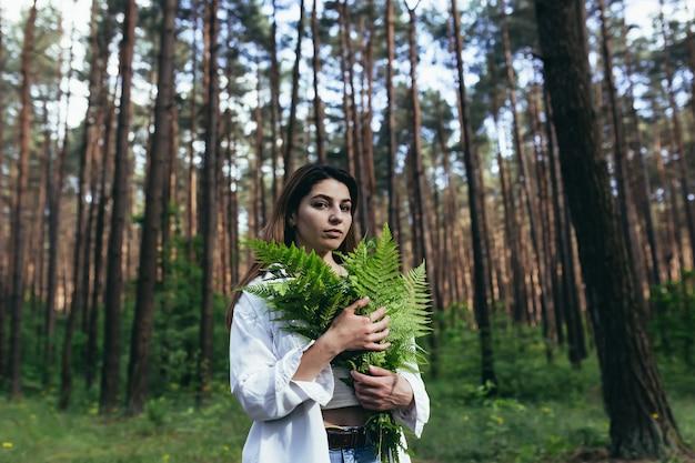 숲 속의 여성이 양치류 꽃다발을 껴안고, 젊은 활동가가 숲을 보호합니다