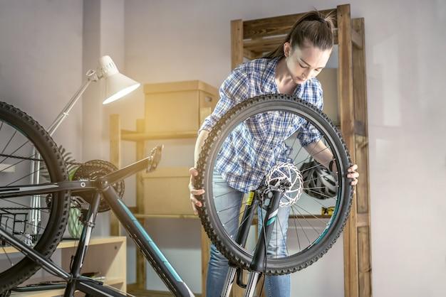 작업장에서 한 여성이 그의 자전거를 분해하고 수리하고 있습니다. 새 시즌을 위한 유지 관리 및 준비의 개념