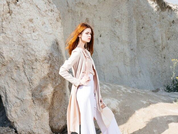 自然と大きな岩の近くでズボンとセーターを着た女性