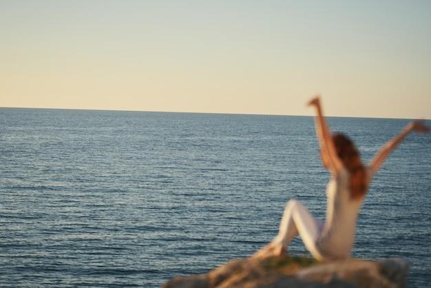 ズボンとtシャツを着た女性が手を上げて海の近くの大きな石の上に座っています