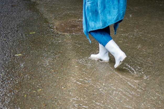 白いゴム長靴を着た女性が雨の中通りを歩いています。水は道路に沿って流れます。秋の雨。