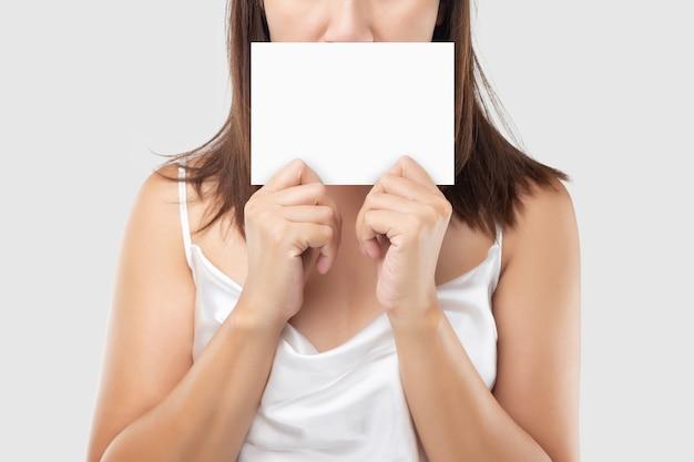 Женщина в белом атласном платье держит белый чистый лист бумаги на светло-сером фоне.