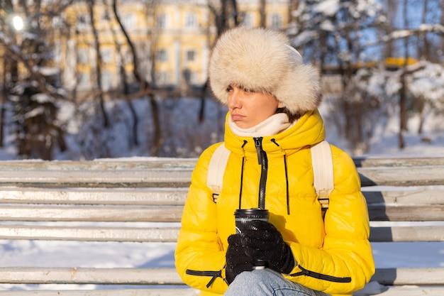 晴れた日に雪に覆われた公園で暖かい服を着た冬の女性はベンチに座って寒さから凍っていて、冬は不幸で、一人でコーヒーを持っています