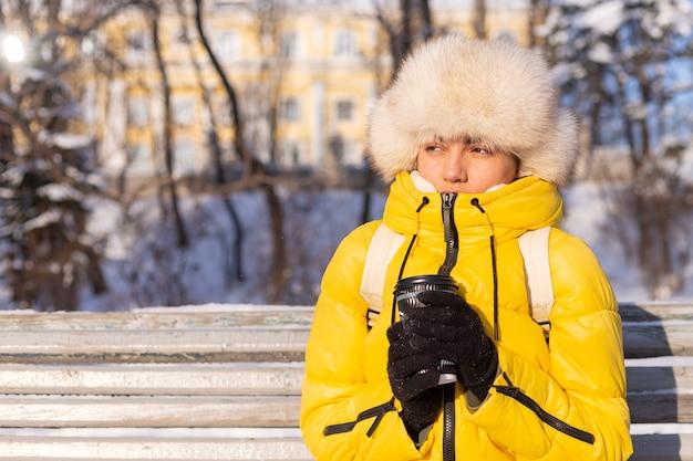 화창한 날 눈 덮인 공원에서 따뜻한 옷을 입은 겨울 여성이 벤치에 앉아 추위에 얼고 겨울에 불행하며 커피를 홀로 들고