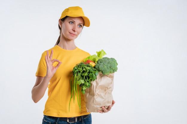 흰색 배경에 음식 패키지를 제공하는 노란색 옷을 입은 여자