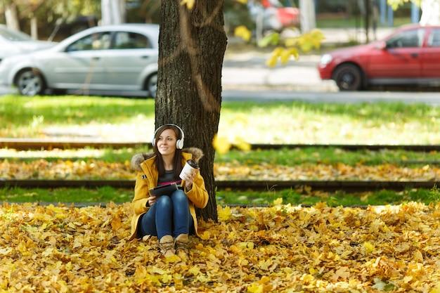 노란 코트와 청바지를 입은 한 여성이 따뜻한 날 가을 도시 공원에서 커피나 차 한 잔과 함께 나무 아래에서 손에 태블릿을 들고 헤드폰을 들고 음악을 듣고 있습니다. 가 황금 잎입니다.