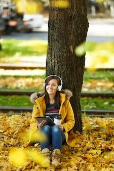 Женщина в желтом пальто и джинсах сидит с чашкой кофе или чая и слушает музыку под деревом с планшетом в руках и наушниками в осеннем городском парке в теплый день. осенние золотые листья.