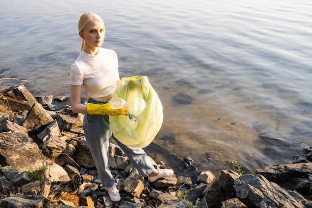 青いゴミ袋を持った黄色い手袋をした女性が湖の岩の多い岸に立っています。彼女は片手で岸を片付け、ゴミを取り除きます。善行は尊敬に値します。