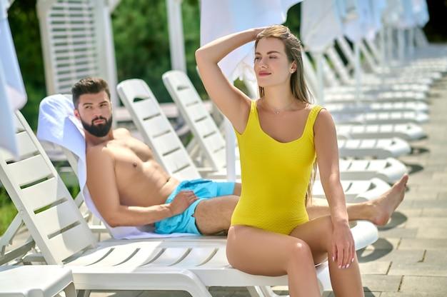 Женщина в желтом купальном костюме ищет детей, пока ее муж загорает