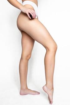 Женщина наносит масло для тела на бедро. капля массажного масла стекает по ноге. концепция личной гигиены.