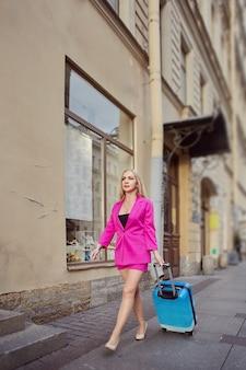 한 여성이 도시 거리를 따라 바퀴에 가방을 들고 있습니다.