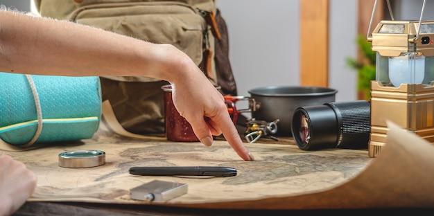 女性がキャンプ用品のある木製のテーブルで世界地図を指差して、次の旅行の場所を選んでいます