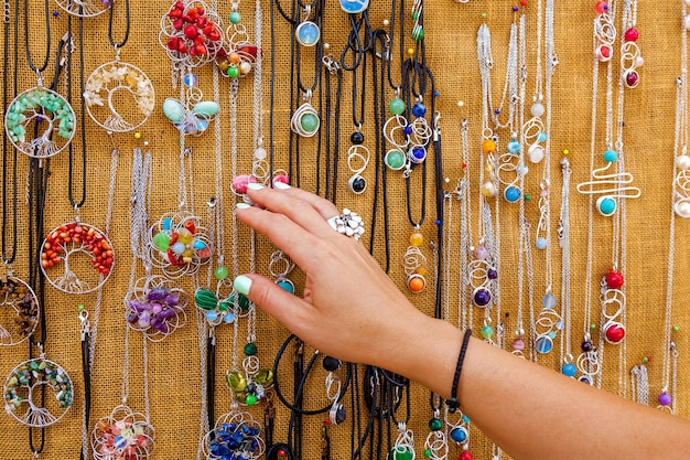 女性はマルタの観光市場でカラフルなネックレスを選んでいます女性のクローズアップビュー