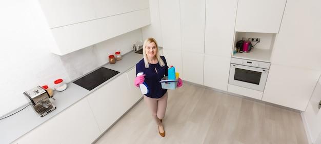 女性が台所を掃除しています。彼女はカメラから目をそらしている。横向きのショット。
