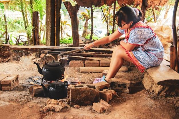 태국 매 클랑 루앙 마을에서 한 여성이 신선한 커피를 끓이기 위해 고대 불을 피우고 있습니다.