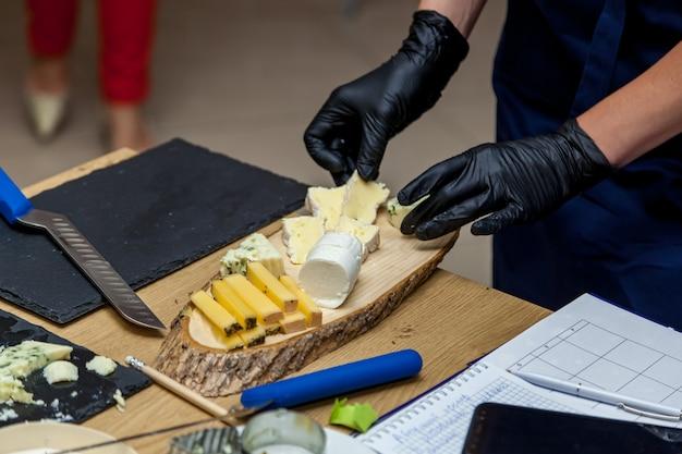 한 여성이 프레젠테이션을 위해 노란색 접시에 칼로 치즈 조각을 자르고 있다