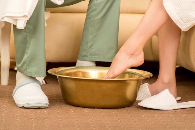 女性が足の治療を洗う前にボウルに足を浸している