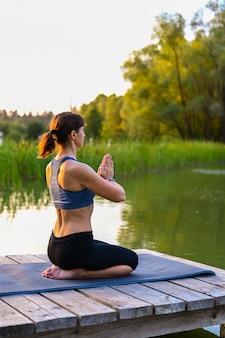 한 여자가 호수에서 운동을 하고 있다. 적합 유지의 개념입니다.