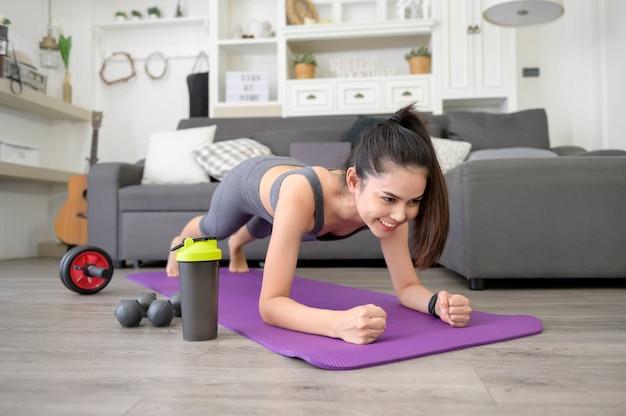 女性はヨガの板をやっていて、リビングルーム、自宅でのフィットネストレーニング、医療技術の概念で彼女のラップトップでオンライントレーニングチュートリアルを見てください。