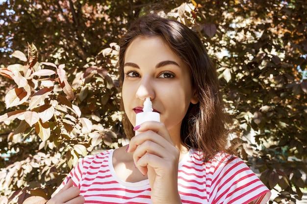 한 여성이 막힌 코에 비강 방울을 떨어 뜨리고 있습니다.