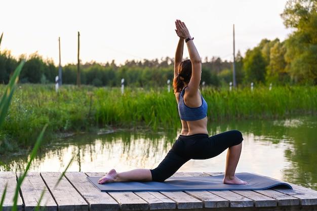 女性は自然の中で体操に従事しています。自然の中でのスポーツ活動の概念。