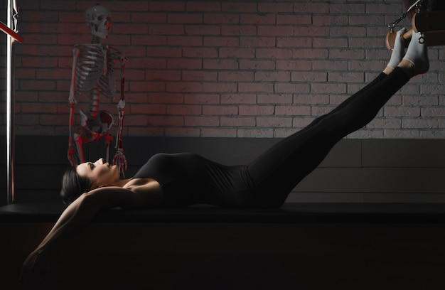 女性はピラティスに従事しています。フィットネスとスポーツ