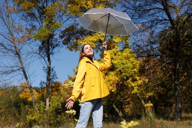晴天の秋、女性は透明な傘に満足