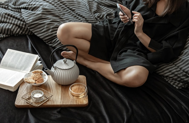 女性は休日にベッドに横たわって、お茶とクッキーで朝食をとっています。