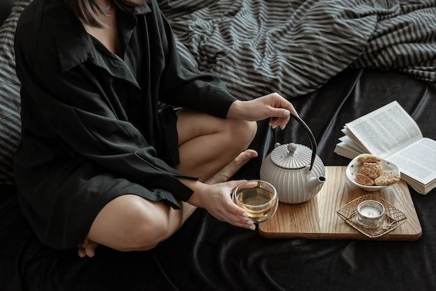 女性が休日にベッドに横になって、お茶とクッキーで朝食をとっています。