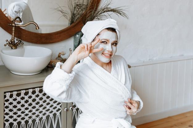 Женщина развлекается и делает лица в ванной с глиняной маской на лице