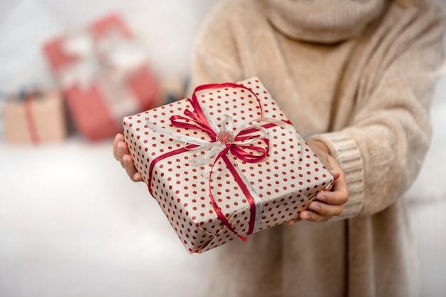 女性が美しいクリスマスプレゼントを持っています。