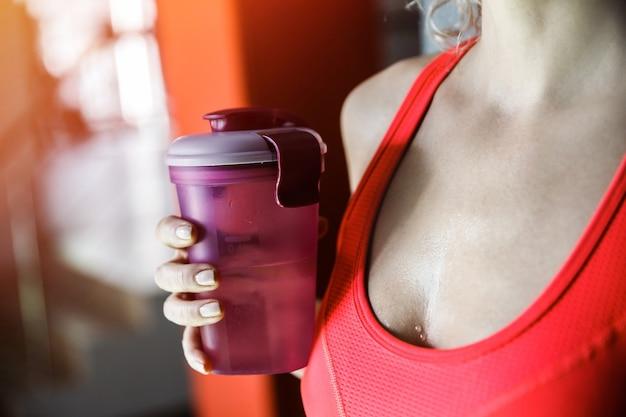 女性が水のクローズアップのボトルを保持しています。