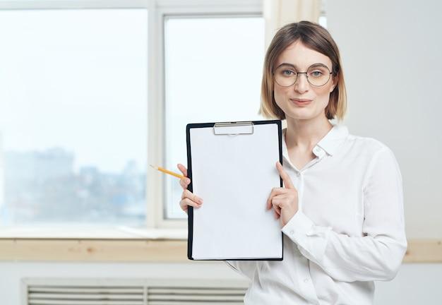 Женщина держит папку с белым листом мокапа и окном на заднем плане.