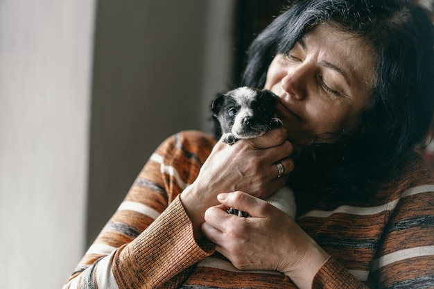 Женщина держит щенка на руках и смеется