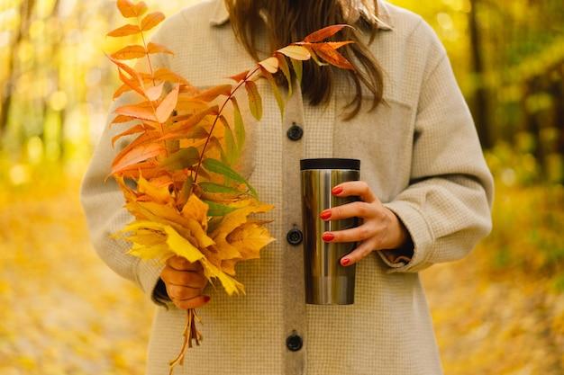 女性がサーモカップを持っており、秋の花束は秋の野外活動を残します