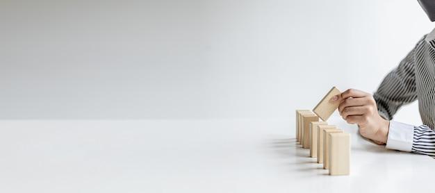 女性が木製のブロックを一列に並べ、センターピースをつかんで完成させます。木製のブロックの配置は、効率的な管理によって事業運営を伝えます。ビジネスアイデア。