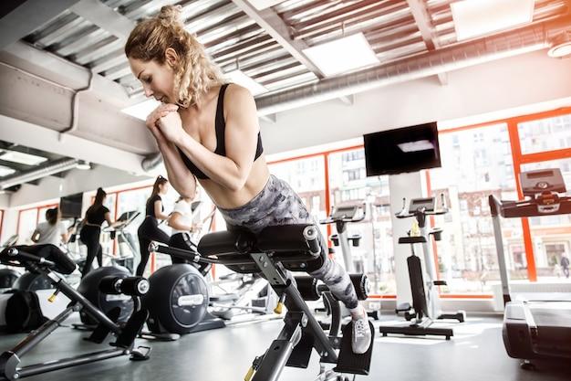 女性がトレーニング器具の上に横たわっています。ジムが背景にあります。