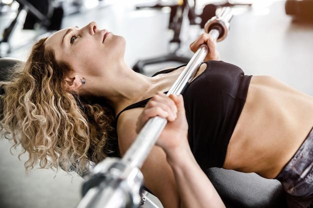 女性がトレーニング装置のクローズアップに横たわっています。彼女はベンチプレスを行使しています。