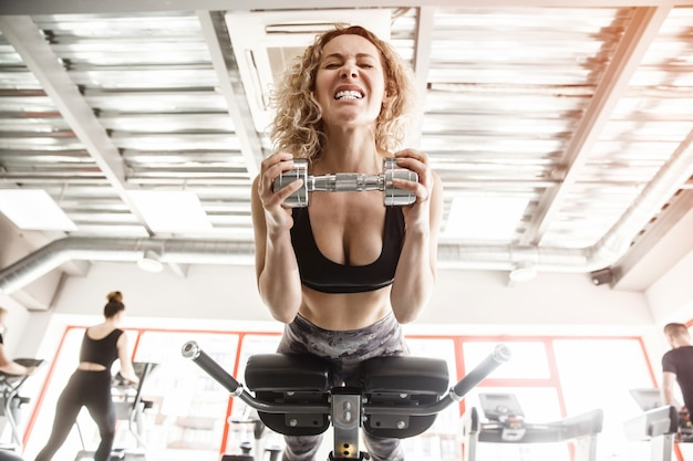 女性がトレーニング器具の上に横たわっています。彼女はダンベルを持って歯をむき出しにしています。